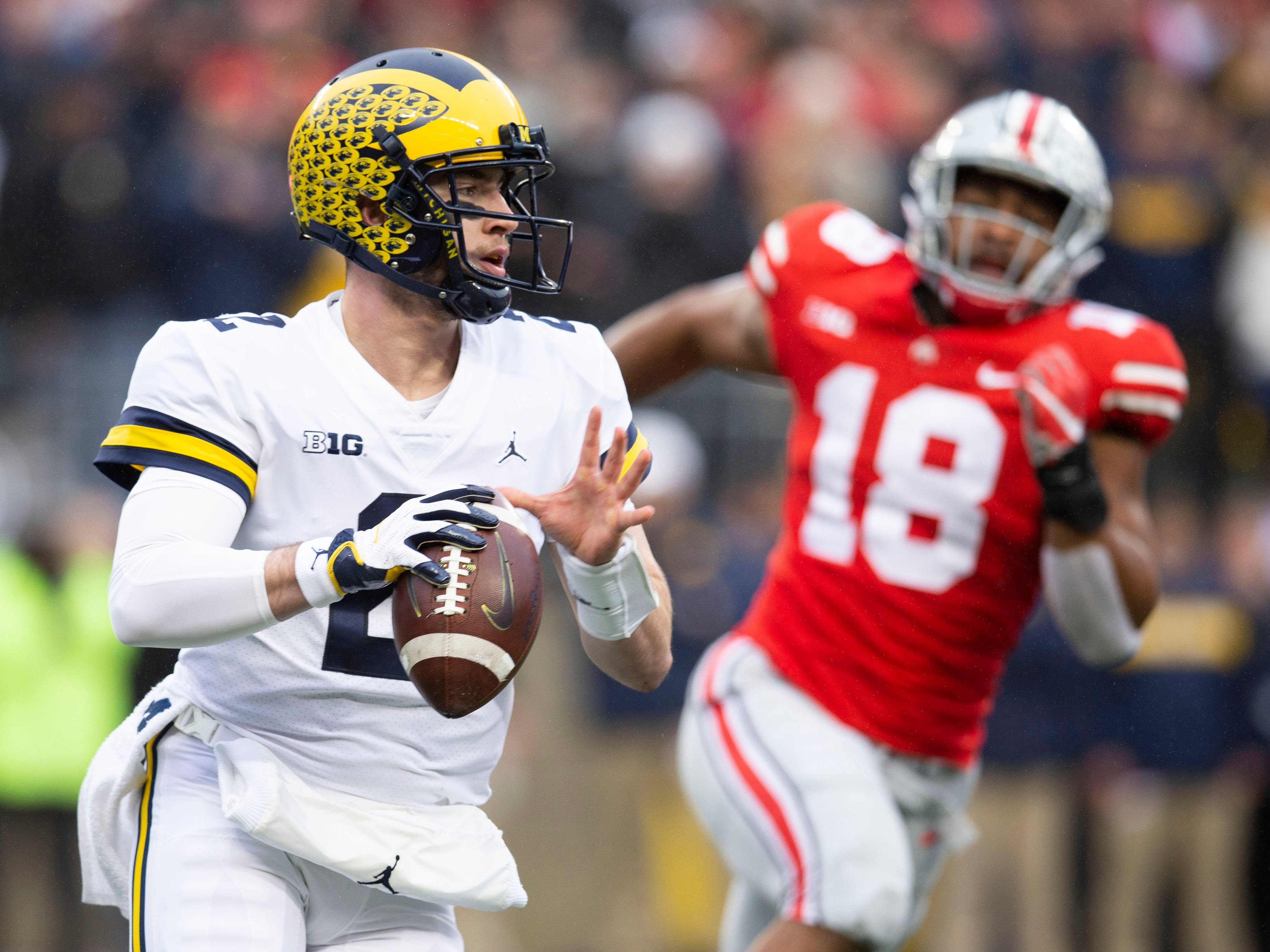 Michigan Wolverines quarterback Shea Patterson (2) looks for an open receiver under pressure from Ohio State Buckeyes defensive end Jonathon Cooper (18) at Ohio Stadium.