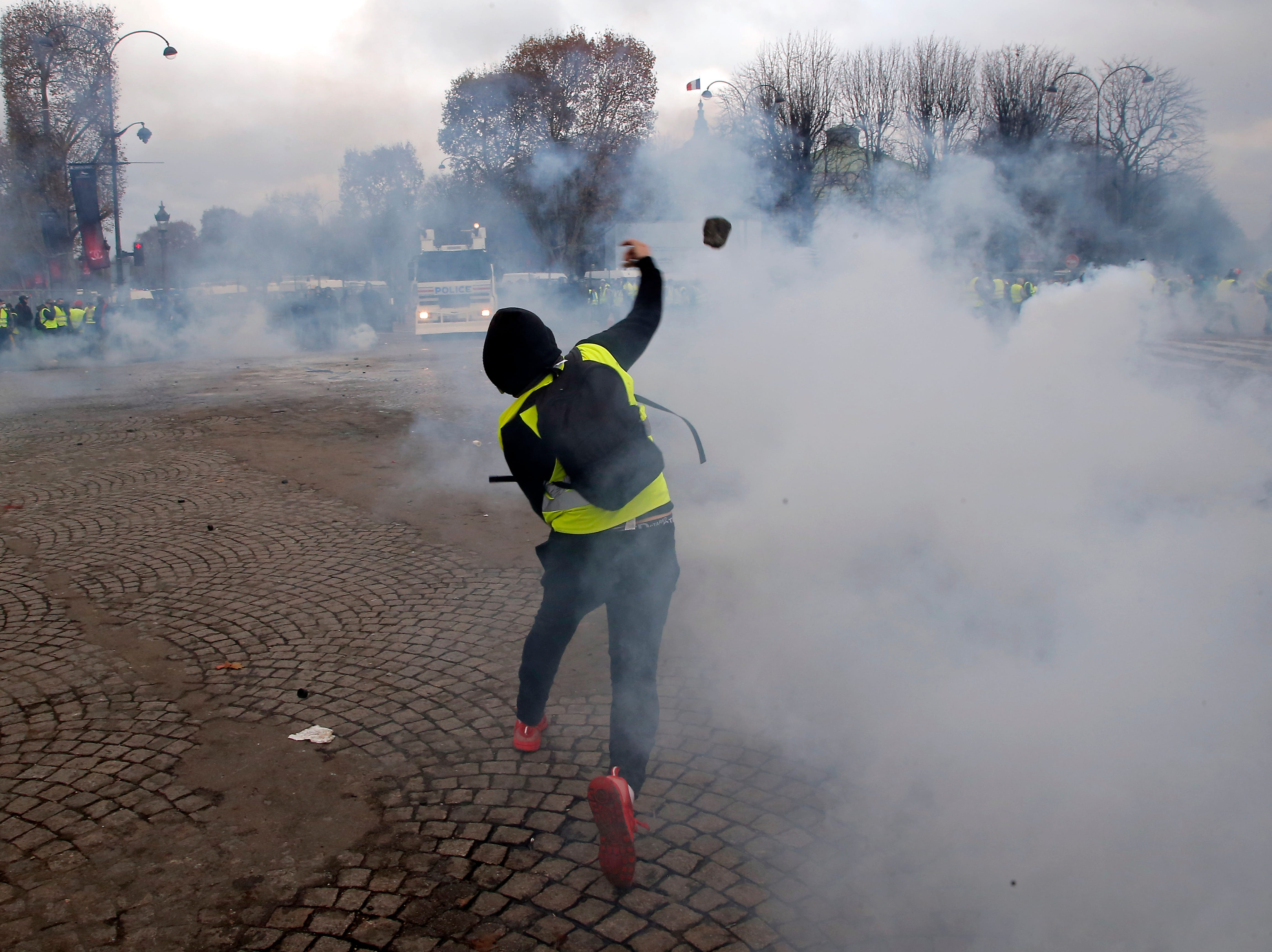 A demonstrator throws a stone to police forces past a burning barricade on the Champs-Elysees avenue during a demonstration against the rising of the fuel taxes, Saturday, Nov. 24, 2018 in Paris. French police fired tear gas and water cannons to disperse demonstrators in Paris Saturday, as thousands gathered in the capital and staged road blockades across the nation to vent anger against rising fuel taxes and Emmanuel Macron's presidency.