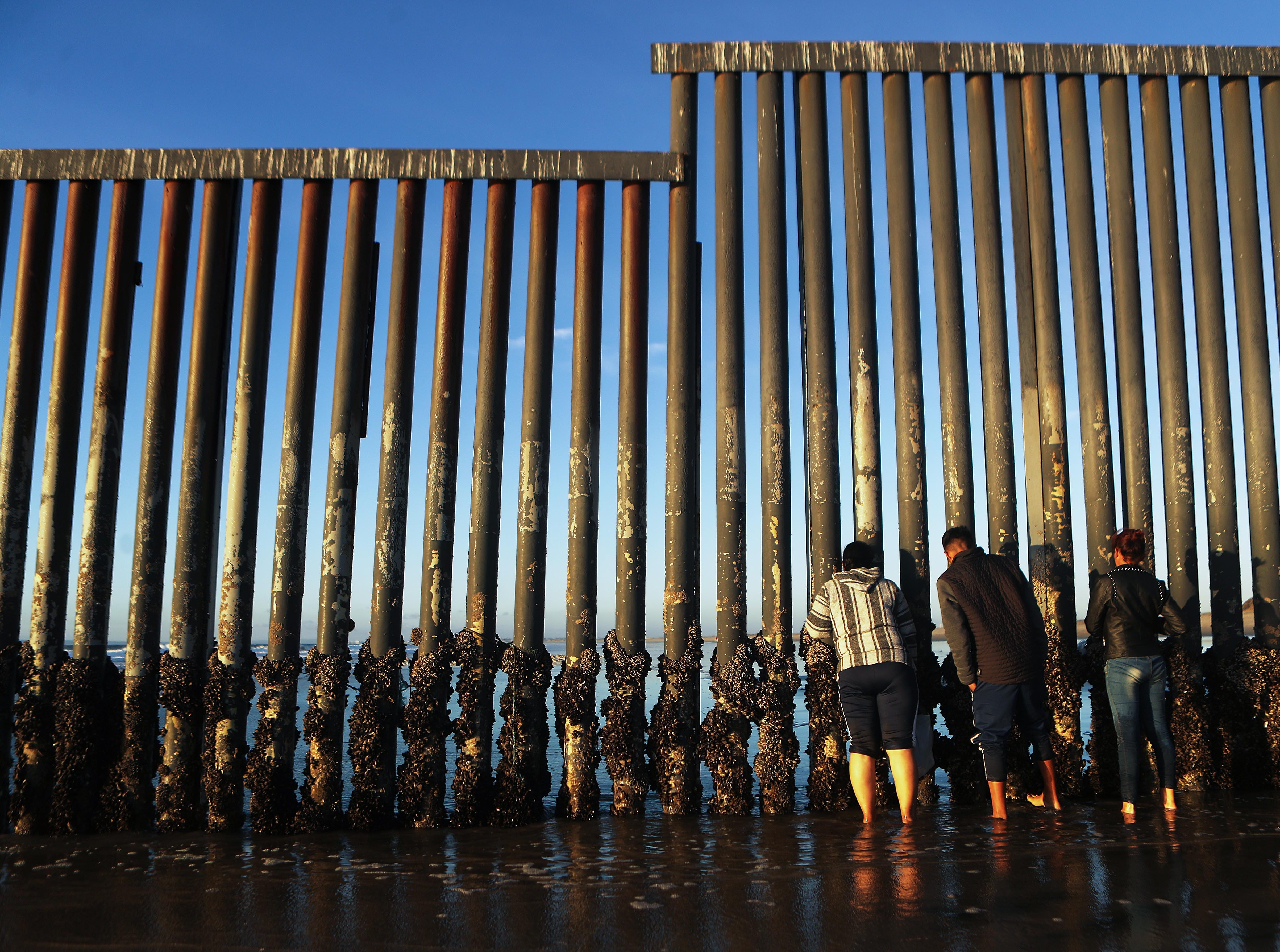 People peer through the U.S.-Mexico border fence, towards San Diego, at the Pacific Ocean, on Nov. 23, 2018 in Tijuana, Mexico.