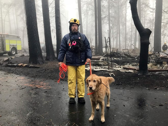 Eric Darling and his dog Wyatt are part of a search team from Orange County in Southern California who are among several teams conducting a second search of a mobile home park after the deadly Camp Fire in Paradise, Calif., Friday, Nov. 23, 2018. The team is doing a second search because there are outstanding reports of missing people whose last known address was at the mobile home park. They look for clues that may indicate someone couldn't get out, such as a car in the driveway or a wheelchair ramp.