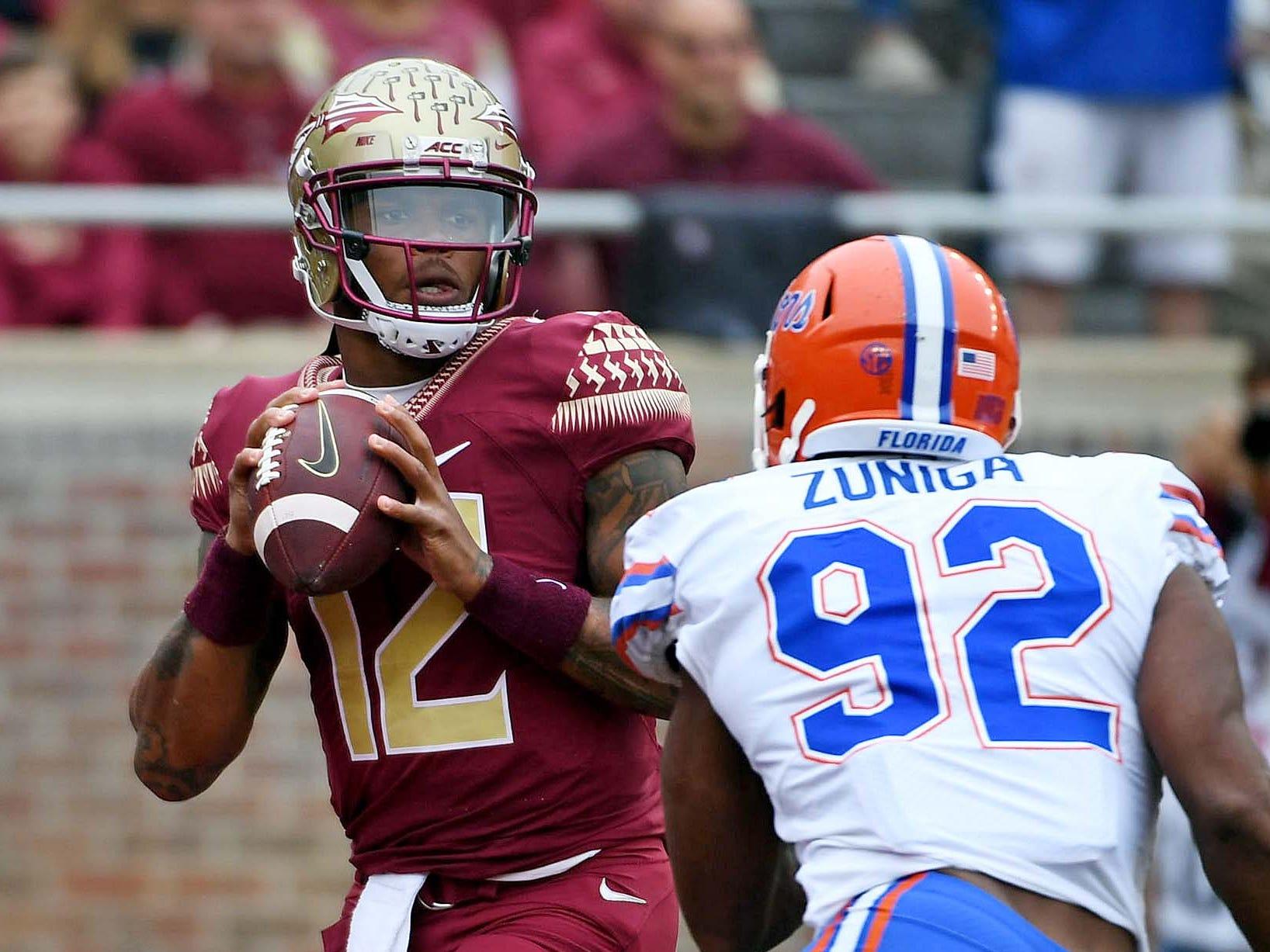 Florida State Seminoles quarterback Deondre Francois (12) looks to throw as Florida Gators defensive lineman Jabari Zuniga (92) closes in during the first half at Doak Campbell Stadium.