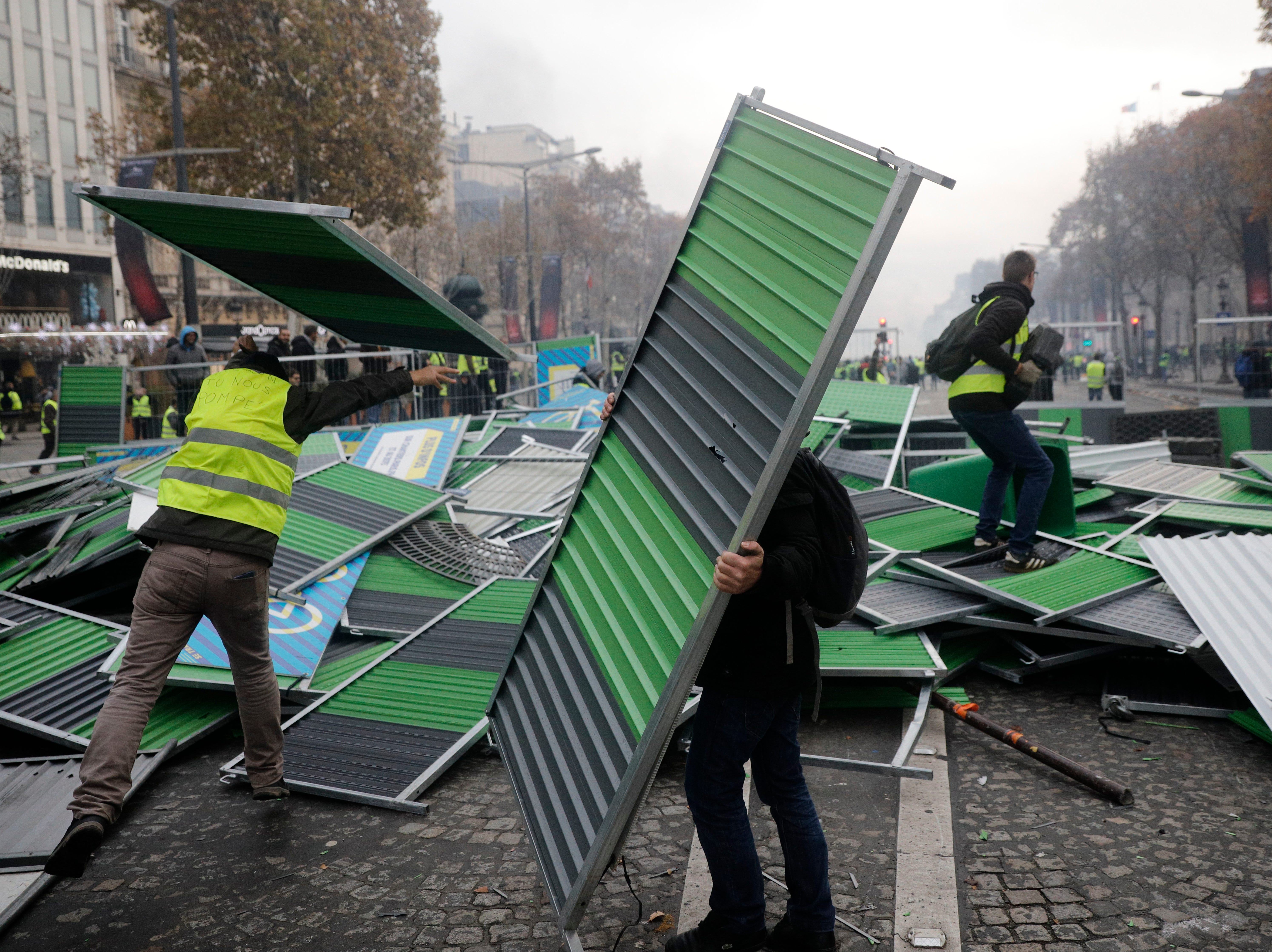 Demonstrators, called the yellow jackets, set up a makeshift barricade on the famed Champs-Elysees avenue as they protest against the rising of the fuel taxes, in Paris, France, Saturday, Nov. 24, 2018.