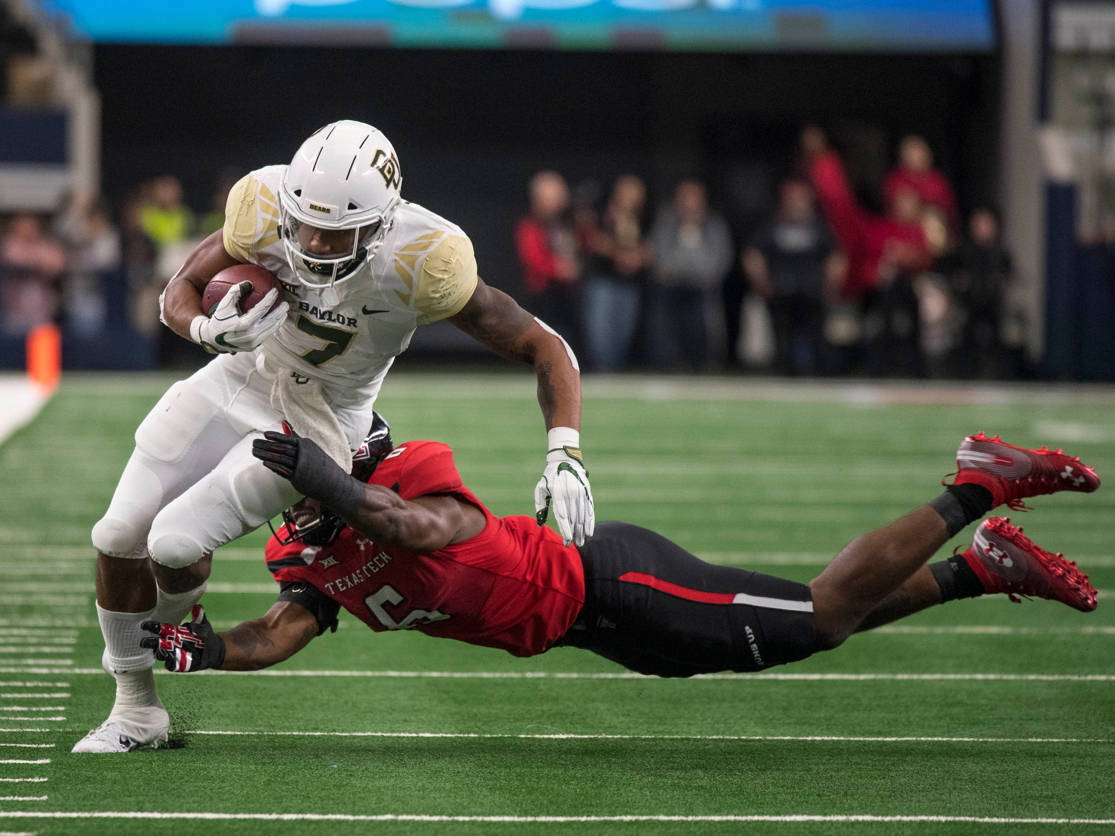 Baylor running back John Lovett tries to elude Texas Tech linebacker Riko Jeffers during the first quarter at AT&T Stadium.