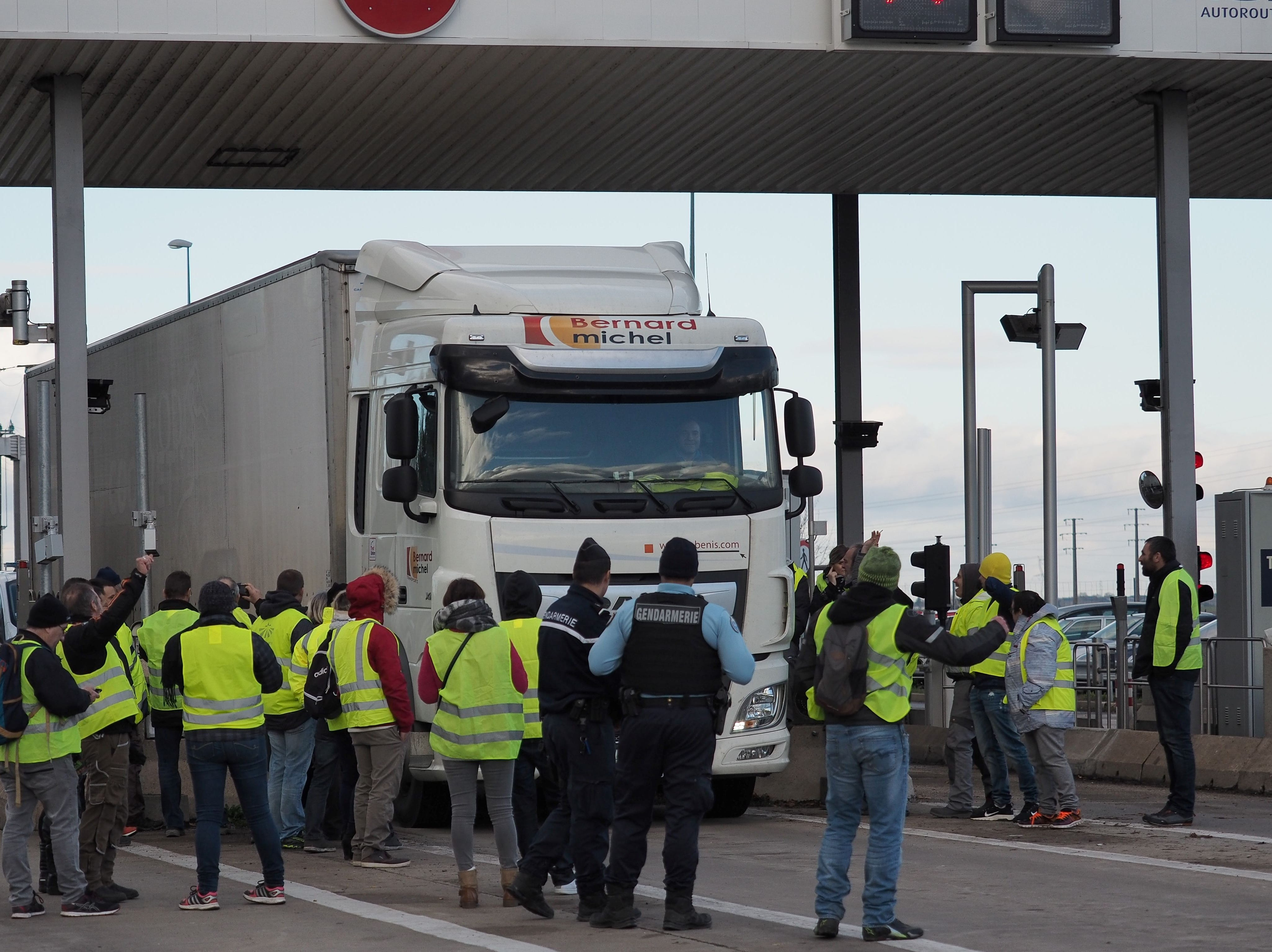 Protestors dressed in Yellow vests let free motorists drive past the toll at the exit of the highway A10 in Blois, central France, on Nov. 24, 2018 to protest against rising oil prices and living costs.