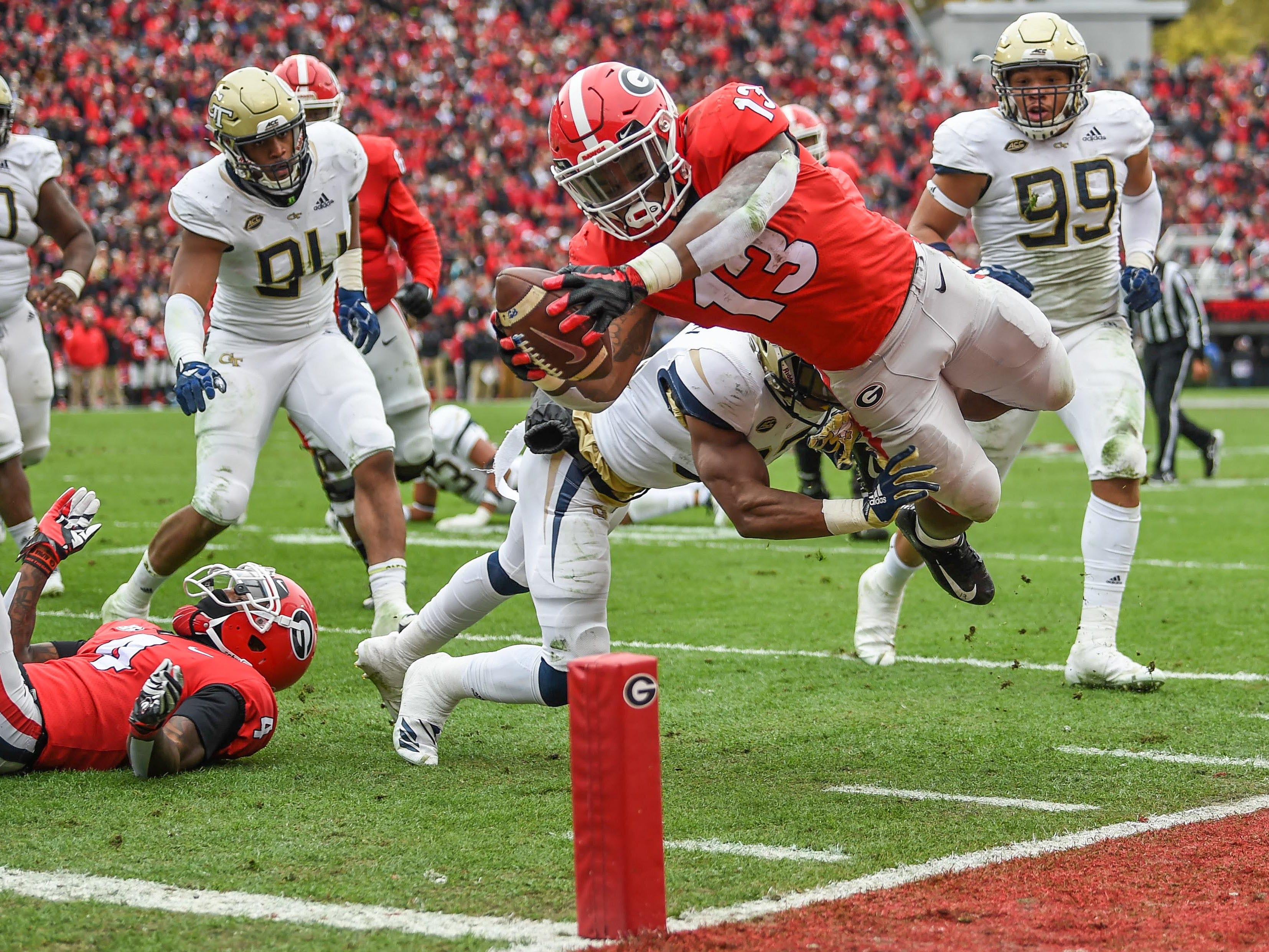Georgia Bulldogs running back Elijah Holyfield (13) dives for a touchdown against the Georgia Tech Yellow Jackets during the first half at Sanford Stadium.