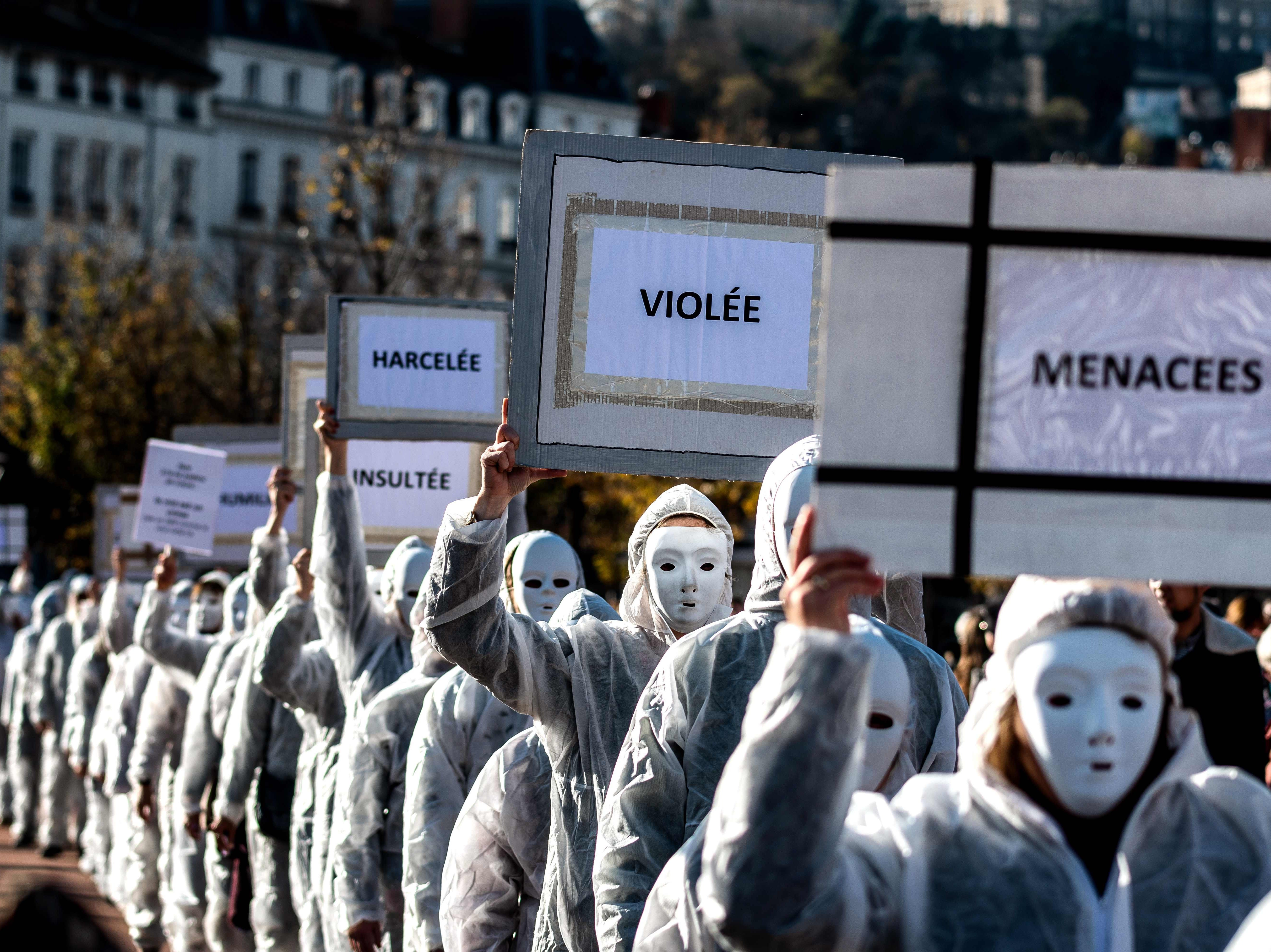 Protestors dressed in white carry placards as they take part in a demonstration in Lyon on Nov. 24, 2018 marking the International Day for the Elimination of violence against Women.
