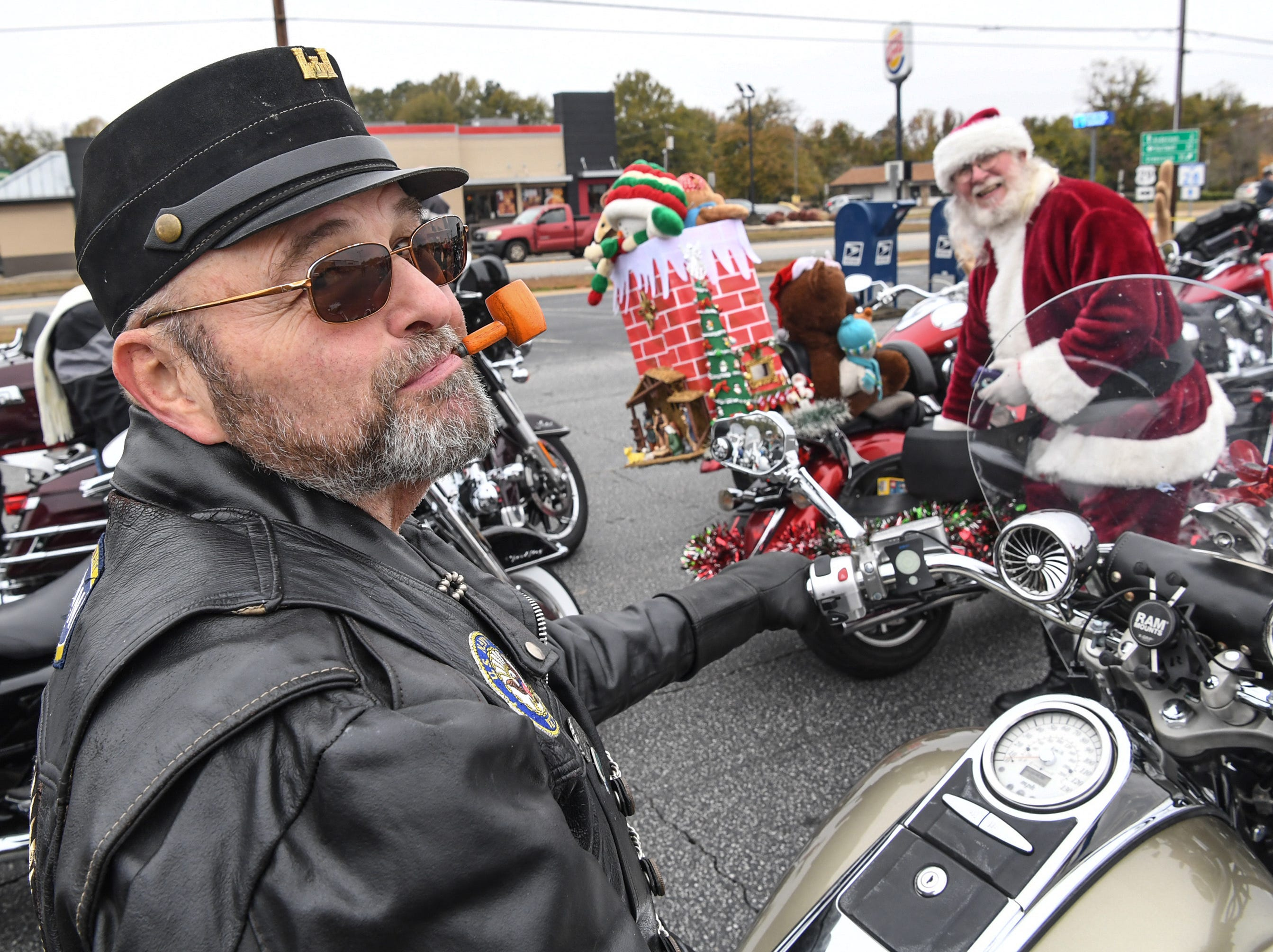 """Jamie Gordon of Easley, left, sits on his motorcycle near Kenny Hooper in a Santa suit before the 38th Jack Hurley Toy Parade in Anderson on Sunday, November 25, 2018. The parade started at White Jones Hardware parking lot in the Watson Village, followed along Main Street to the Civic Center of Anderson where toys were donated to Anderson Cares and Shares. Organizer Robert """"Little Man"""" Fagg said about 350 families are helped out with toys for Christmas."""