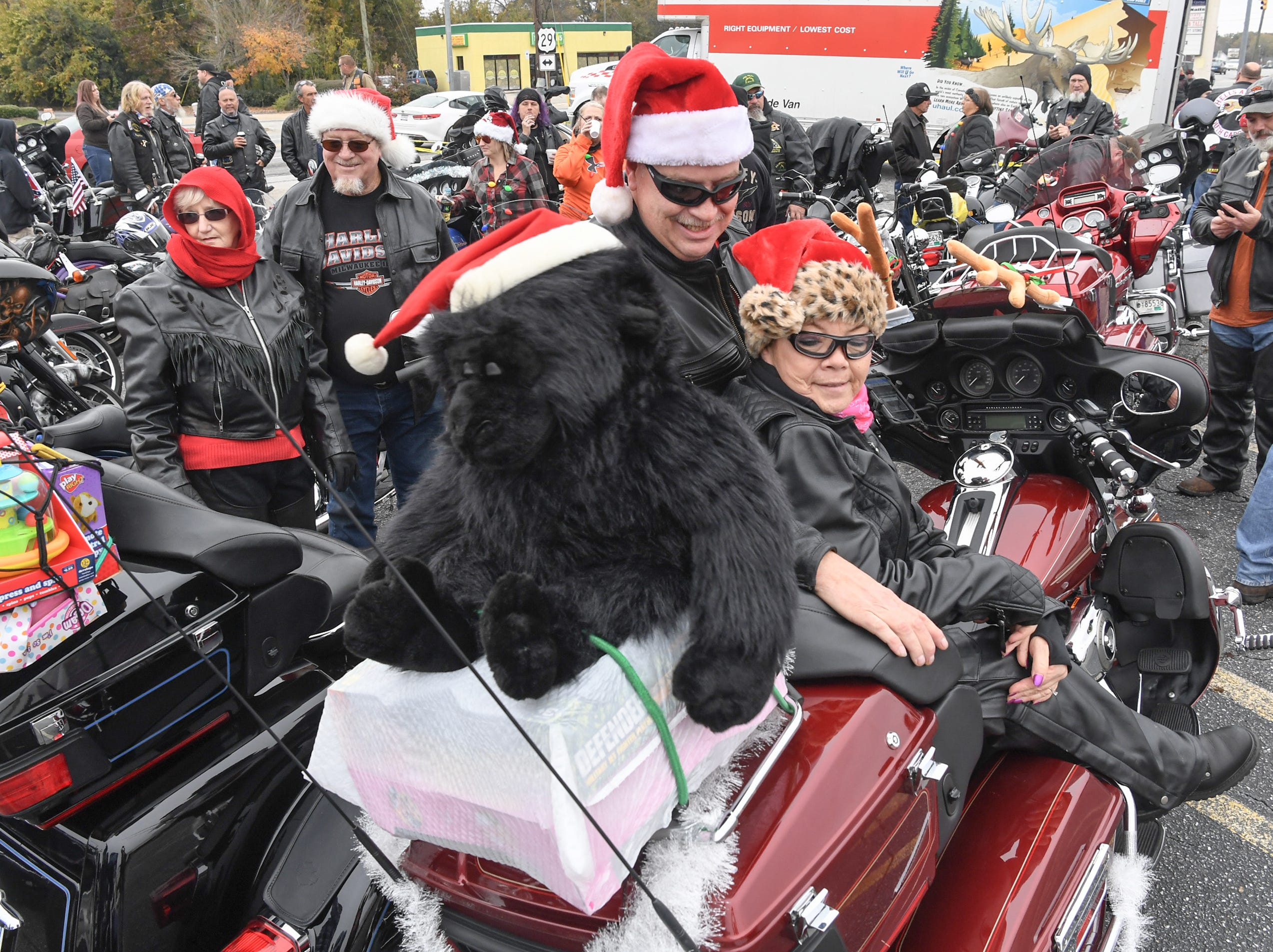 """Martin Nash of Anderson places a red bow on his motorcycle near Sheri Nash, left, near Milton and Rachael Nash, right, before the 38th Jack Hurley Toy Parade in Anderson on Sunday, November 25, 2018. The parade started at White Jones Hardware parking lot in the Watson Village, followed along Main Street to the Civic Center of Anderson where toys were donated to Anderson Cares and Shares. Organizer Robert """"Little Man"""" Fagg said about 350 families are helped out with toys for Christmas."""