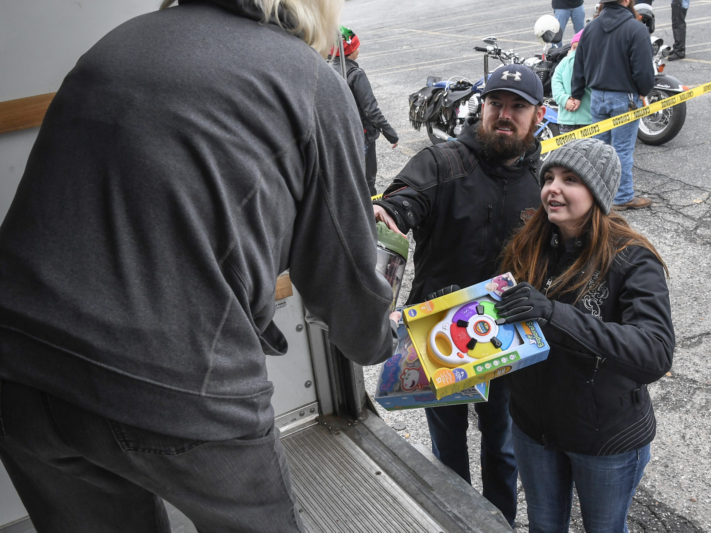 """Matthew and Valerie Wilson of Abbeville bring toys to Debbie Wilbanks of White Jones Hardware, before the 38th Jack Hurley Toy Parade in Anderson on Sunday, November 25, 2018. The parade started at White Jones Hardware parking lot in the Watson Village, followed along Main Street to the Civic Center of Anderson where toys were donated to Anderson Cares and Shares. Organizer Robert """"Little Man"""" Fagg said about 350 families are helped out with toys for Christmas."""