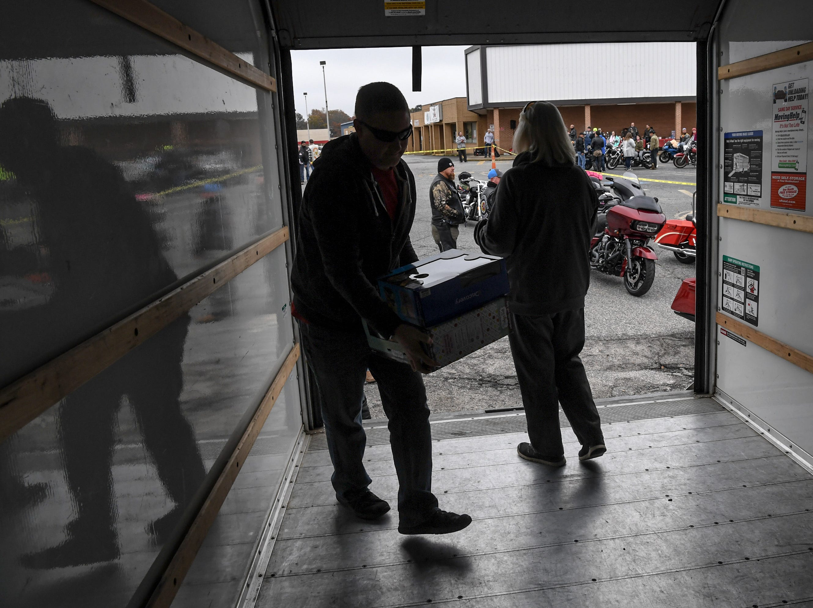 """Keith Dunham, left, and Debbie Wilbanks, right, of White Jones Hardware in Anderson wait for toys to be donated before the 38th Jack Hurley Toy Parade in Anderson on Sunday, November 25, 2018. The parade started at White Jones Hardware parking lot in the Watson Village, followed along Main Street to the Civic Center of Anderson where toys were donated to Anderson Cares and Shares. Organizer Robert """"Little Man"""" Fagg said about 350 families are helped out with toys for Christmas."""