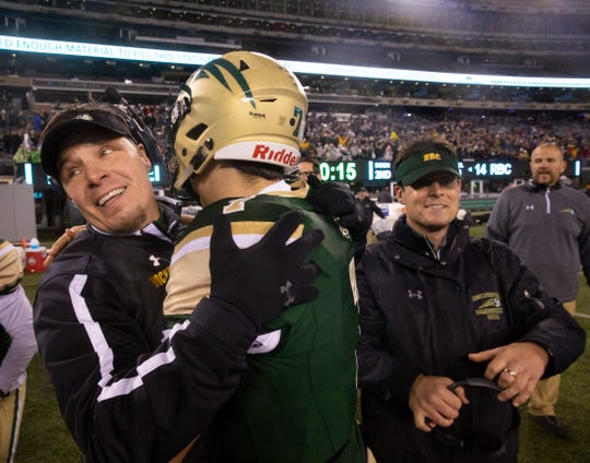 Red Bank Catholic coach Frank Edgerly (left) celebrates the Caseys' NJSIAA Non-Public Group III championship with his son Ryan Saturday night at MetLife Stadium.  Red Bank Catholic assistant coach Joe Gallagher is on the right.