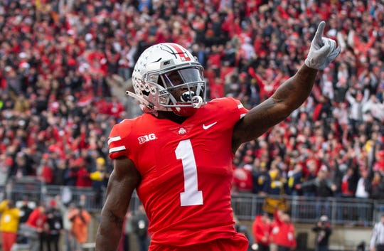 Ohio State receiver Johnnie Dixon celebrates his 31-yard touchdown catch in the second quarter of Saturday's 62-39 win over Michigan.