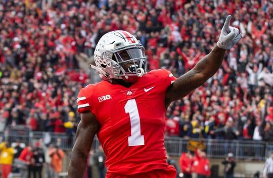 Ohio State receiver Johnnie Dixon celebrates his 31-yard touchdown catch in the second quarter of Saturday's 62-39 win over Michigan.