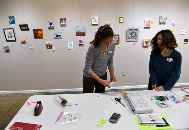 """Laura Greenwood (left), the manager of the 1818 Arthouse, prepares the show """"Tiny Art!"""" with the help of Hannah DeLeon. The Snyder gallery's show of small artwork will be up until Dec. 22."""