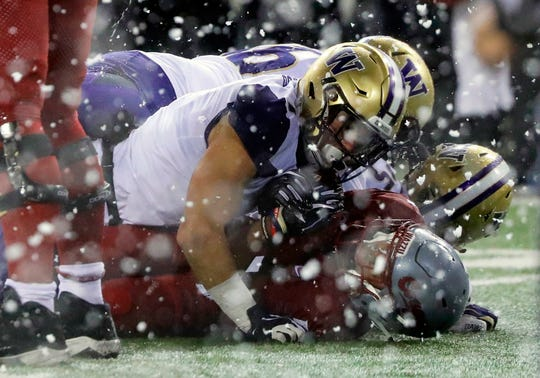 Washington State's Travell Harris (lower right) is tackled by Washington safety Taylor Rapp as snow flies during the first half of the Huskies' 28-15 Apple Cup win.