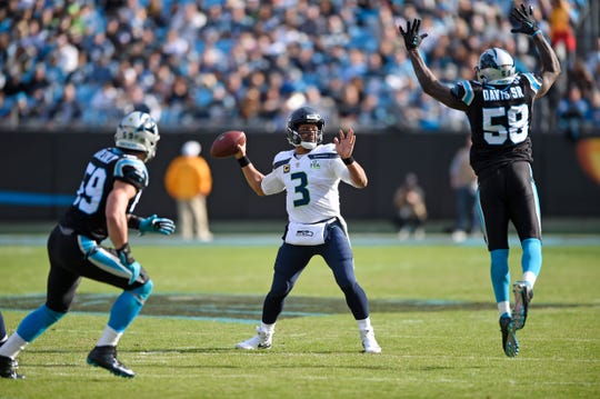Seattle Seahawks' Russell Wilson (3) tries to pass over Carolina Panthers' Thomas Davis (58).