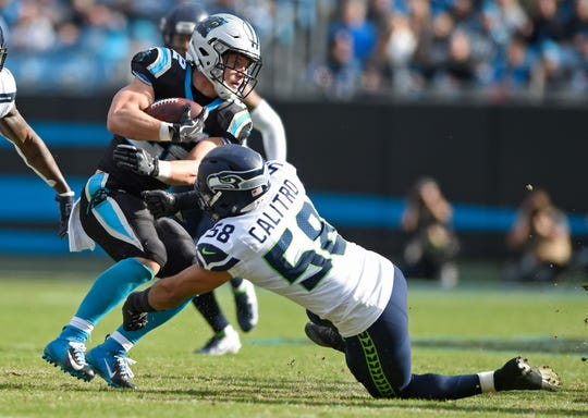 Carolina Panthers' Christian McCaffrey (22) is stopped by Seattle Seahawks' Austin Calitro (58).