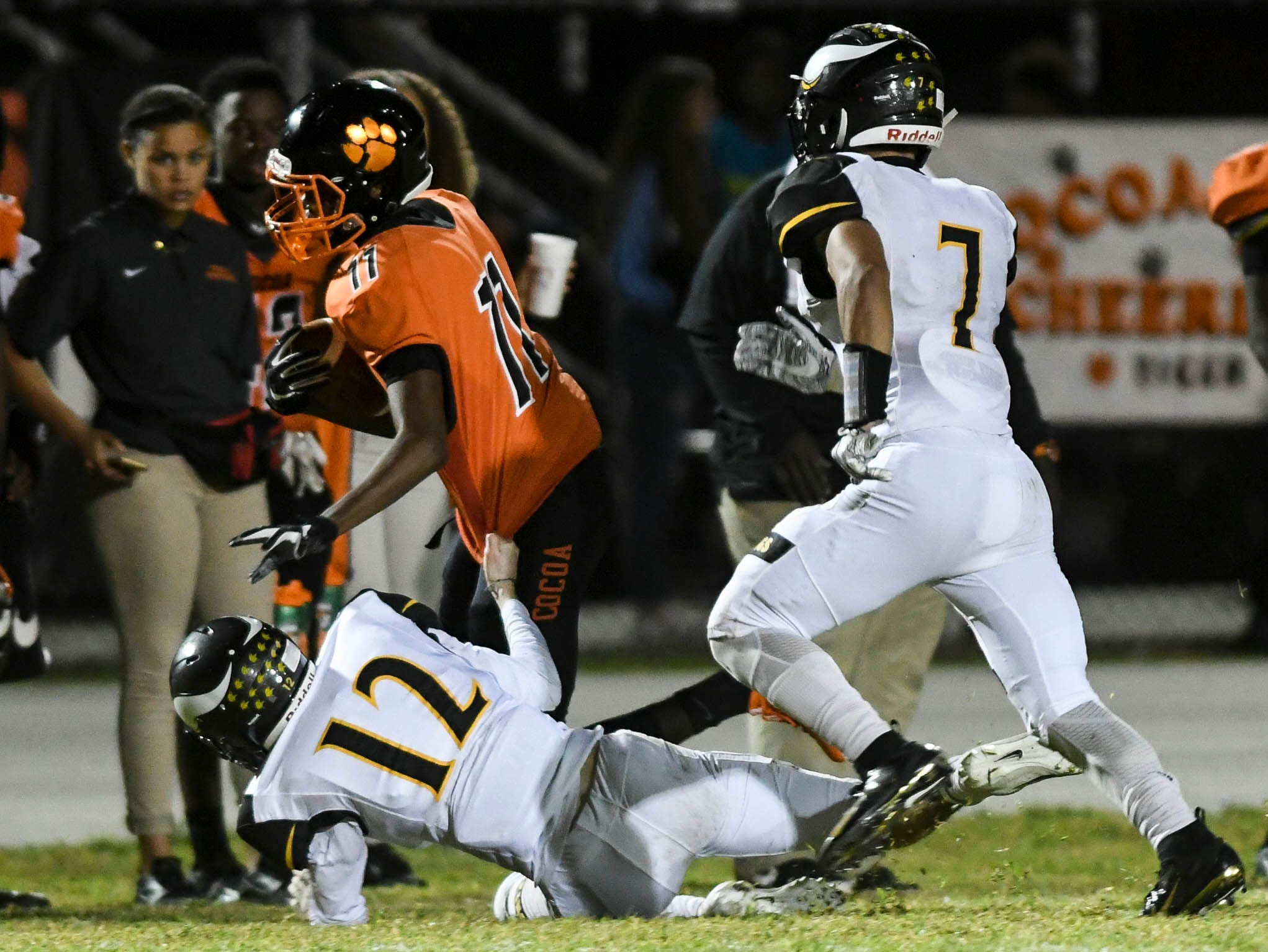 Jamari Williams of Cocoa is brought down by Blake Williams (12) and Dominic Febels of Bishop Verot during Friday's game.