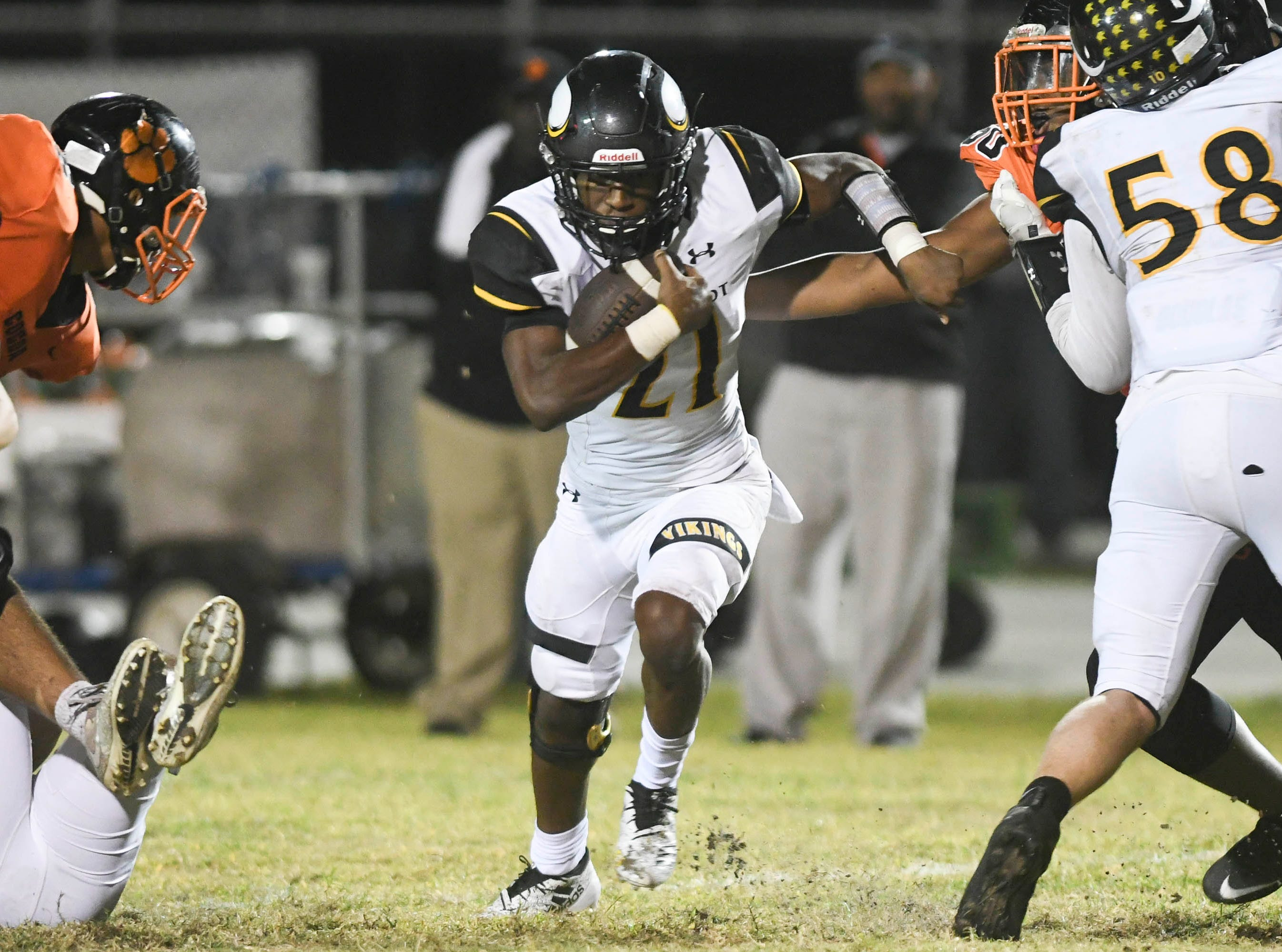 Terry Lindsey of Bishop Verot runs through a hole in the Cocoa defense during their game Friday.
