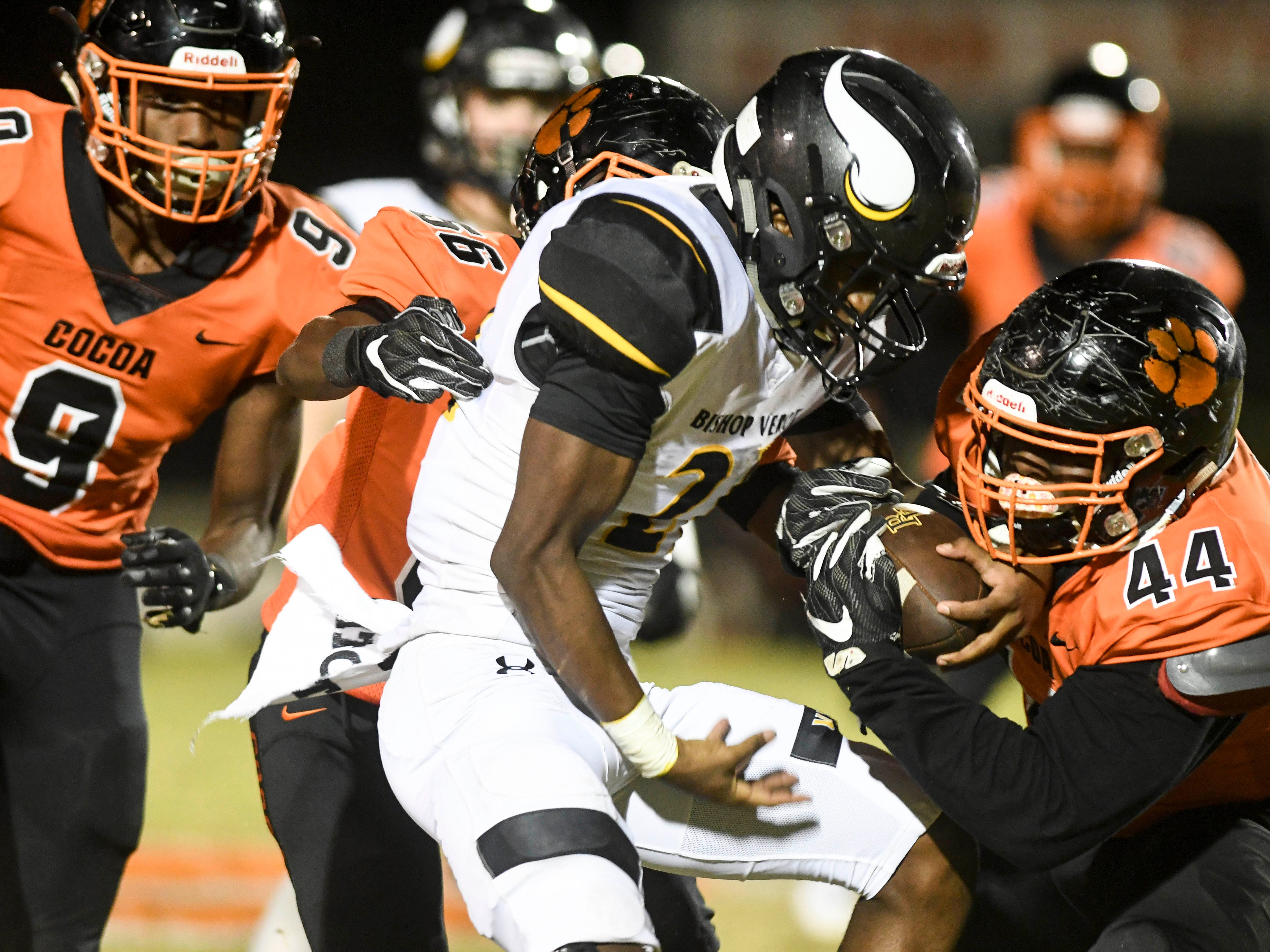 Cocoa defenders Marquise Freeman (9) AJ Williams (56) and Dajavon White take down Bishop Verot ballcarrier Terry Lindsey during Friday's game at Blake Stadium.