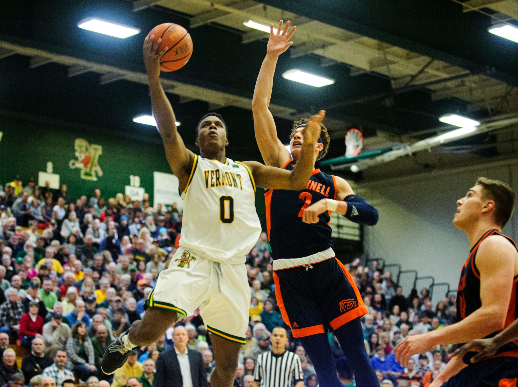 Vermont guard Stef Smith (0) leaps past Bucknell's Walter Ellis (2) for a lay up during the men's basketball game between the Bucknell Bison and the Vermont Catamounts at Patrick Gym on Sunday afternoon November 25, 2018 in Burlington.