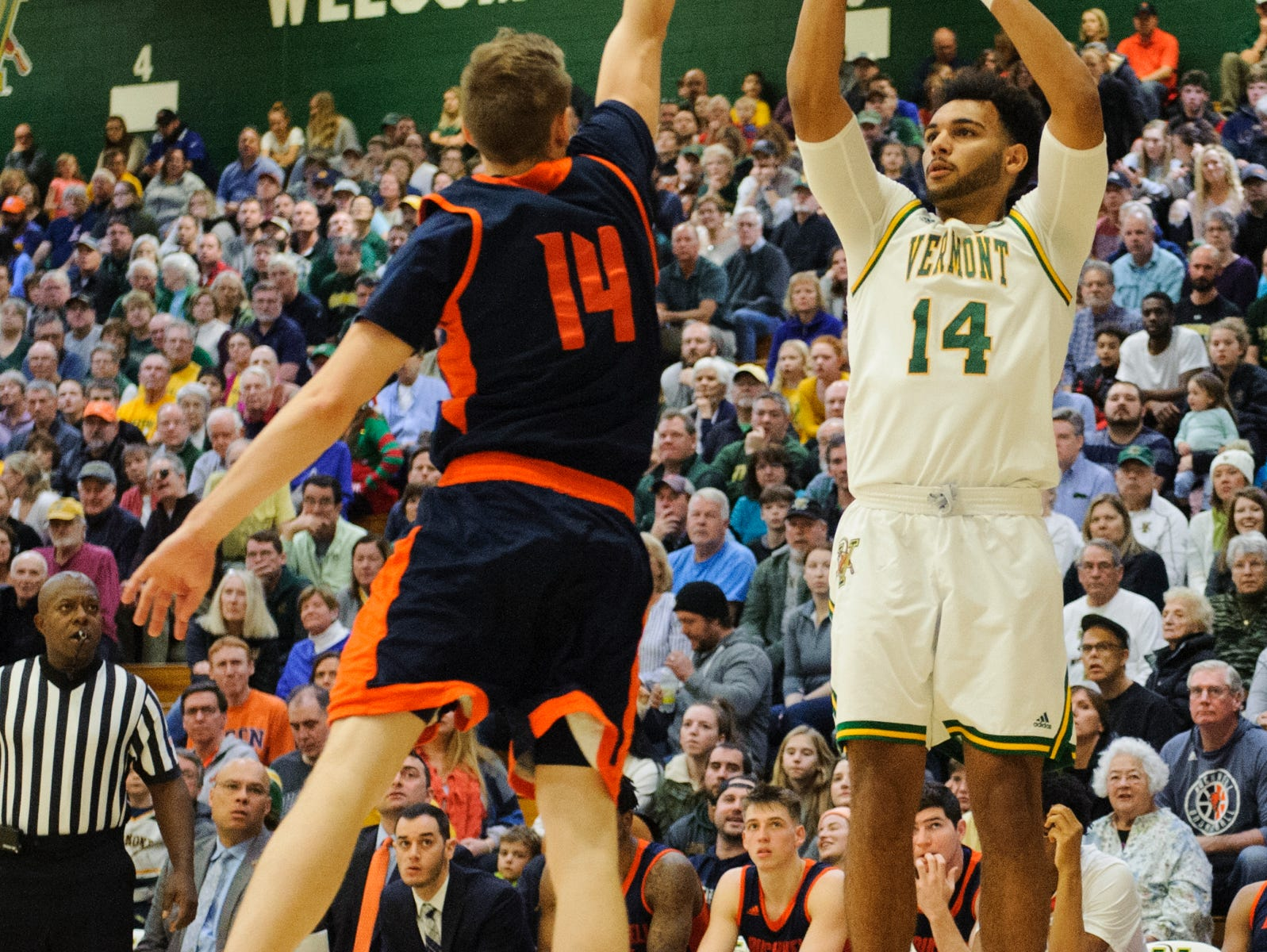 Vermont forward Isaiah Moll (14) shoots a three pointer over Bucknell's Ben Robertson (14) during the men's basketball game between the Bucknell Bison and the Vermont Catamounts at Patrick Gym on Sunday afternoon November 25, 2018 in Burlington.