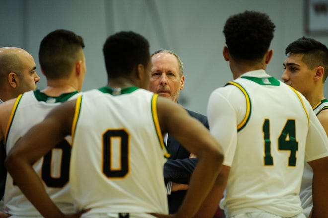 Vermont coach John Becker talks to the team during a timeout during the men's basketball game between the Bucknell Bison and the Vermont Catamounts at Patrick Gym on Sunday afternoon.