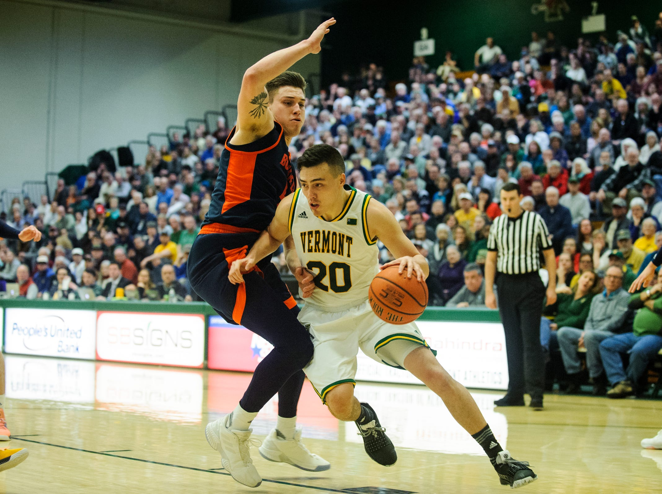 Vermont guard Ernie Duncan (20) drives to the hoop past Bucknell's Nate Sestina (4) during the men's basketball game between the Bucknell Bison and the Vermont Catamounts at Patrick Gym on Sunday afternoon November 25, 2018 in Burlington.