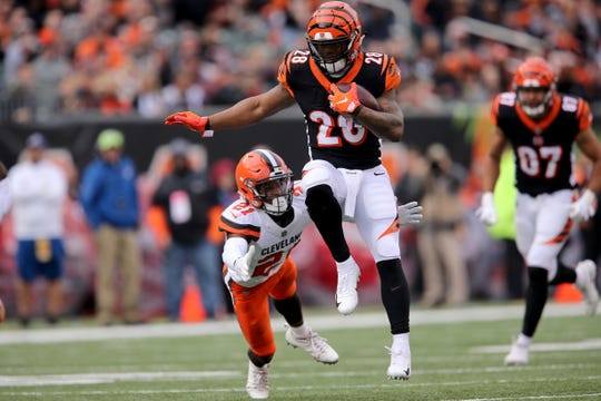 Cincinnati Bengals running back Joe Mixon (28) avoids a tackle by Cleveland Browns cornerback Denzel Ward (21) in the second quarter of an NFL Week 12 football game, Sunday, Nov. 25, 2018, at Paul Brown Stadium in Cincinnati.