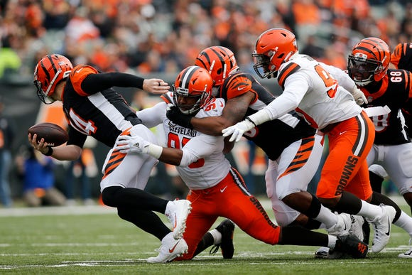 Cincinnati Bengals quarterback Andy Dalton (14) breaks a tackle as he runs for a first down in the second quarter of the NFL Week 12 game between the Cincinnati Bengals and the Cleveland Browns at Paul Brown Stadium in downtown Cincinnati on Sunday, Nov. 25, 2018.