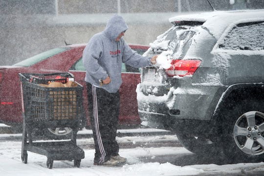 Anthony Walters of Mission, Kan., wipes snow from a vehicle before loading groceries into it on Sunday, Nov. 25, 2018, in Roeland Park, Kan.