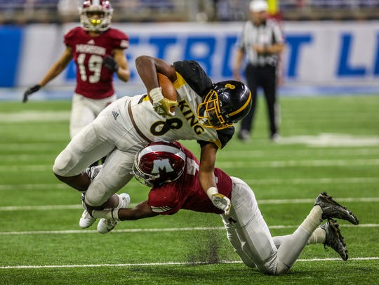 Detroit King's Peny Boone is tackled by  Muskegon's Ray Williams, during the Division football state title at Ford Field on Saturday, Nov. 24, 2018.