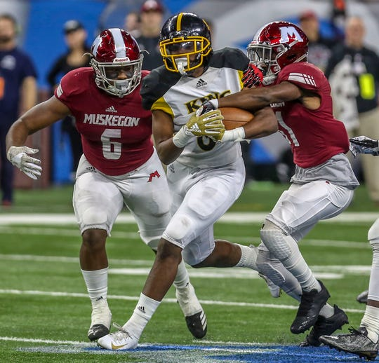 Detroit King's Peny Boone runs with the ball after a catch against Muskegon's Robert Carson, right, and Ali'vonta Wallace during the Division football state title at Ford Field on Saturday, Nov. 24, 2018.