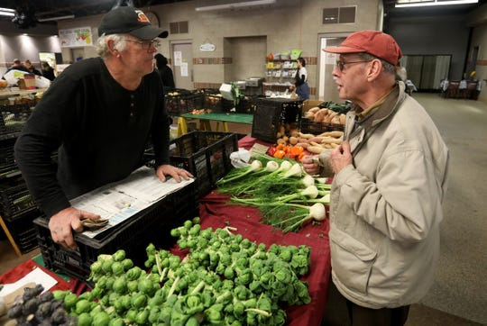 From left, Don Van Houtte, owner of Van Houtte Farms, chats with fellow farmer Jin Van Denburgeh at the Royal Oak Farmers Market on Saturday, November 24, 2018.Van Houtte is unhappy that the new city hall building is going up in the parking lot adjacent to the market.