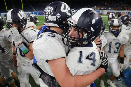 Hudsonville Unity Christian Austin Schuiteman hugs Josh Brinks after winning the Division 5 MHSAA State Championship at Ford Field in Detroit on Saturday, Nov. 24, 2018.