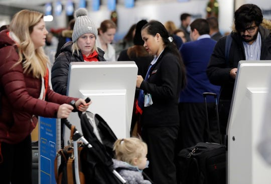 Travelers check in at the American Airlines self ticket counter at O'Hare International Airport in Chicago, Sunday, Nov. 25, 2018. More than 350 flights already canceled ahead of blizzard-like storm taking aim at Chicago.