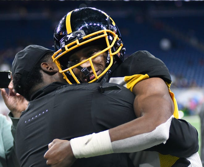 Detroit King quarterback Dequan Finn is congratulated by team personnel near the end of the championship game.