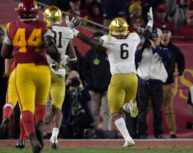 Notre Dame running back Tony Jones Jr., right, celebrates as he runs in for a touchdown as Southern California defensive lineman Malik Dorton gives chase during the second half.
