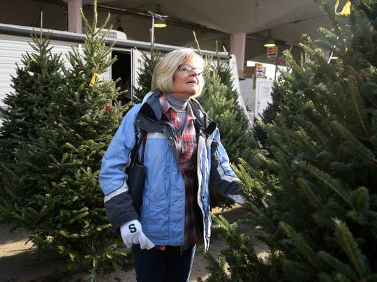 Julie Hill, 59, of Port Huron browses through the lot of  Christmas trees looking for the right one, as she does her annual tree shopping.at Eastern Market in Detroit on Sunday.