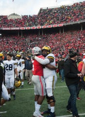 Ohio State running back Mike Weber (Detroit Cass Tech) is embraced by Michigan center Cesar Ruiz on the field after the game.