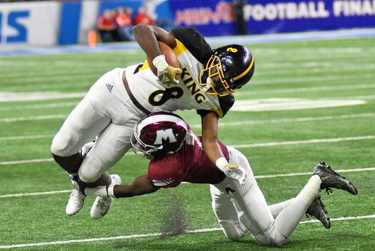 Detroit King running back Peny Boone (8), left, rushes for yardage and is tackled by Muskegon linebacker Kolbie Lewis (7) during the fourth quarter.