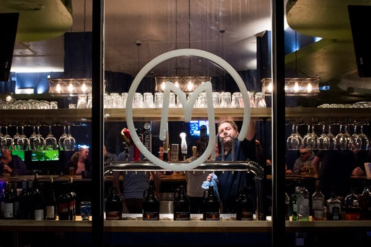 Bartender Byran Sumner reaches for a glass to serve a customer at Myriad Brewing located in the lobby of The McCurdy Wednesday, Nov. 21, 2018.