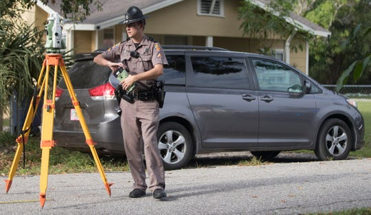 Florida Highway Patrol officers process the death scene of a 22-month-old child on Bessie Avenue in Fort Myers on Sunday The child died after being run over by a van, pictured, in the driveway of the child's home. FHP is still investigating the incident.