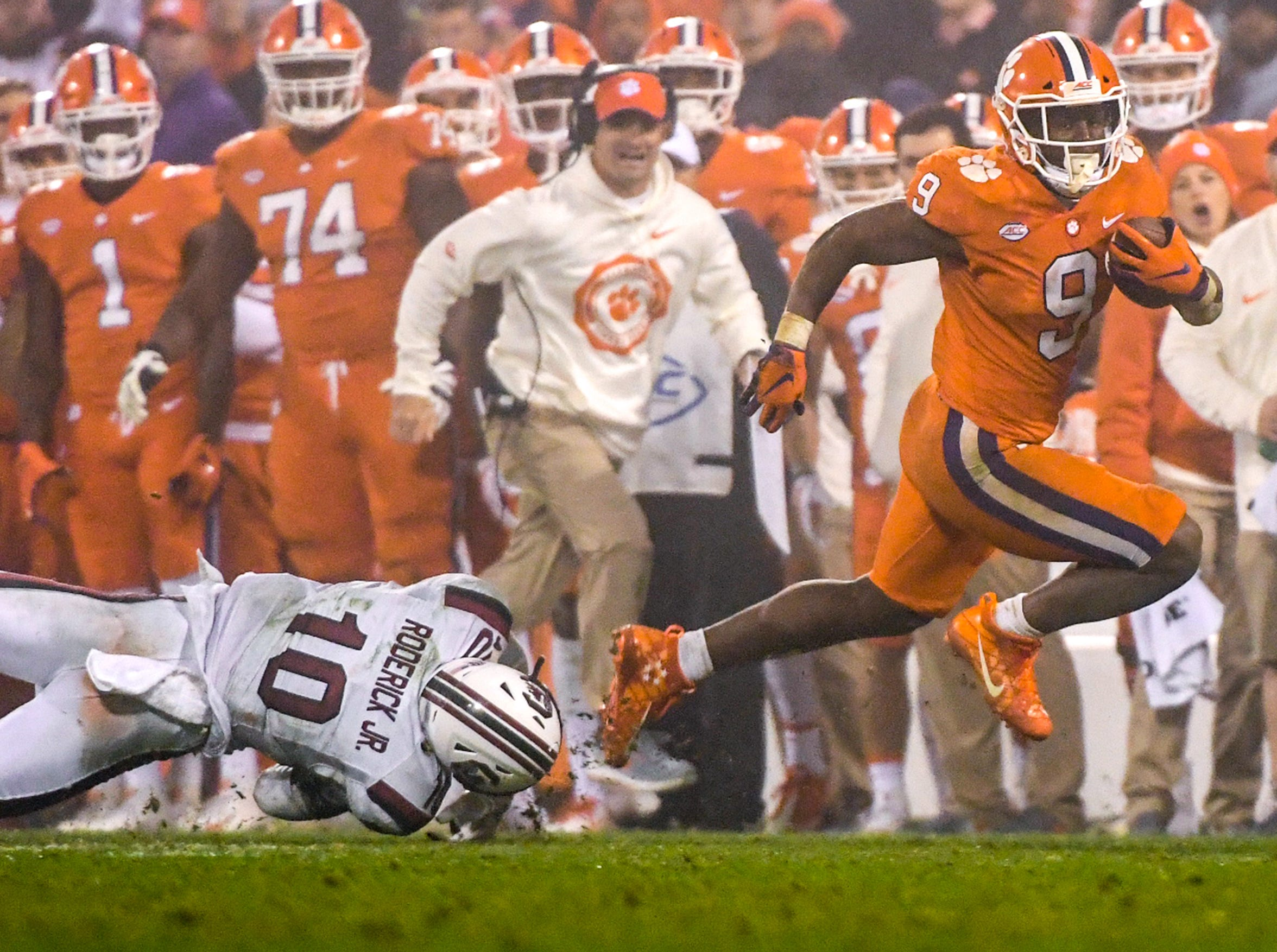 Clemson running back Travis Etienne (9) runs by South Carolina defensive back R.J. Roderick(10) during the fourth quarter in Memorial Stadium on Saturday, November 24, 2018.