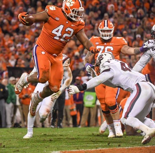Clemson defensive lineman Christian Wilkins (42) jumps over South Carolina linebacker Sherrod Greene(44) for a touchdown during the second quarter in Memorial Stadium on Saturday, November 24, 2018.