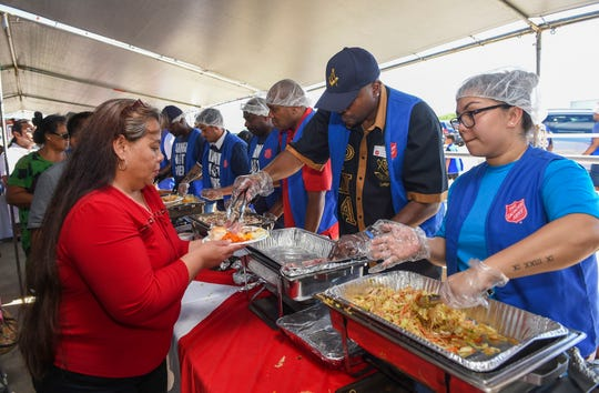 Volunteers serve meals to event attendees during The Salvation Army's 22nd annual Thanksgiving Feast at their Tiyan headquarters, Nov. 25, 2018.