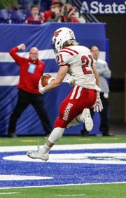 New Palestine's Colby Jenkins (21) celebrates a touchdown during the IHSAA Class 5A football State Championship game between New Palestine High School and Decatur Central High School, held at Lucas Oil Stadium on Saturday, Nov. 24, 2018.    ?