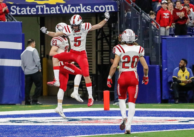 New Palestine's Colby Jenkins (21) celebrates a touchdown with teammates New Palestine's Eric Roudebush (5), and New Palestine's Maxen Hook (20), during the IHSAA Class 5A football State Championship game between New Palestine High School and Decatur Central High School, held at Lucas Oil Stadium on Saturday, Nov. 24, 2018.   ?