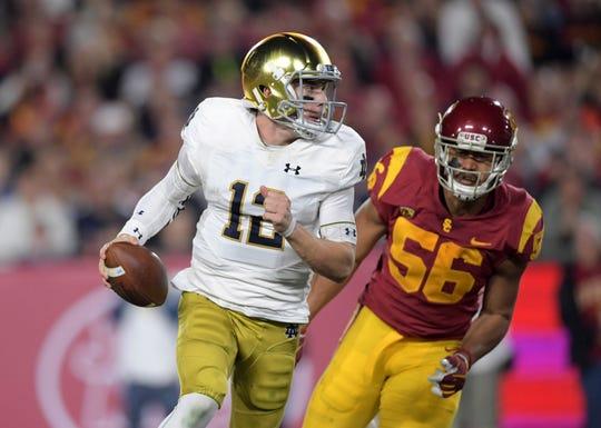 Notre Dame Fighting Irish quarterback Ian Book (12) is pressured by Southern California Trojans linebacker Jordan Iosefa (56) in the second quarter at Los Angeles Memorial Coliseum.