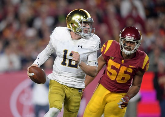 Notre Dame Fighting Irish quarterback Ian Book (12) is pressured by Southern California Trojans linebacker Jordan Iosefa (56) in the second quarter at Los Angeles Memorial Coliseum.